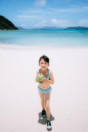 Cute preschool girl with coconut walking on tropical beach, Okinawa, Japan - gettyimageskorea