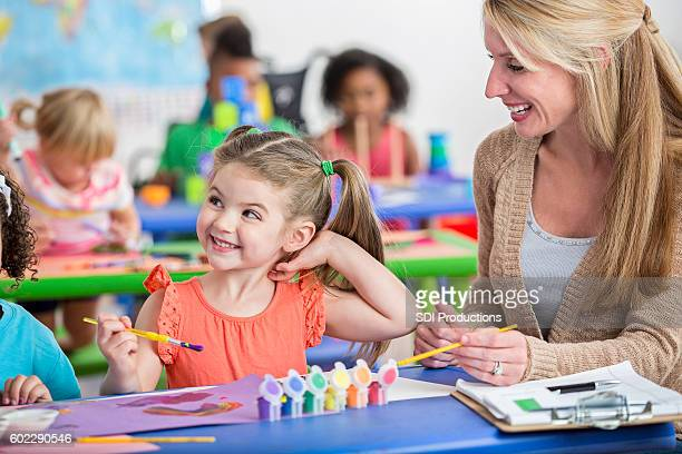 Cute preschool girl with pigtails painting in daycare with teacher