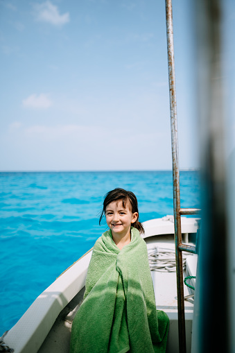 Cute preschool girl wrapped in towel, sitting on boat with blue tropical sea - gettyimageskorea