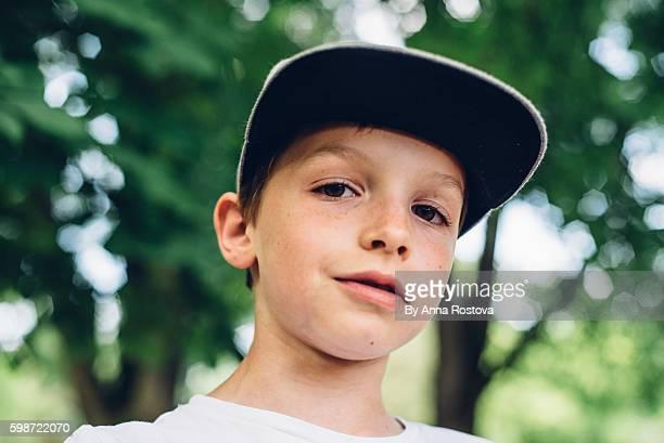 Cute preteen boy in baseball cap looking at camera