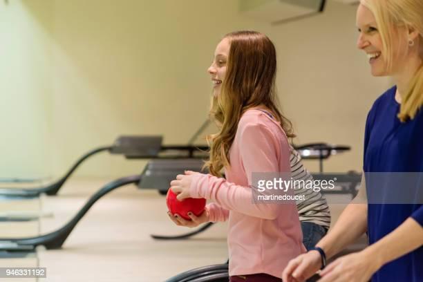 """linda garota pré-adolescente jogando boliche com a mulher madura. - """"martine doucet"""" or martinedoucet - fotografias e filmes do acervo"""