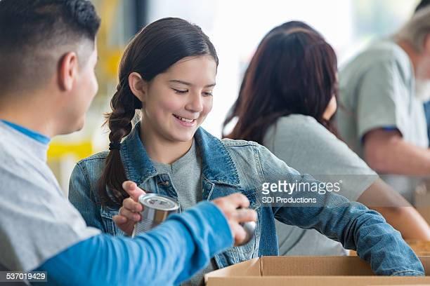 Cute preteen girl volunteering in food bank to sort donations