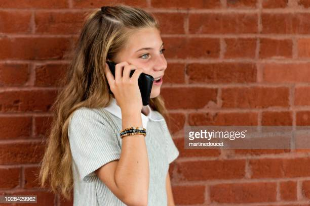 "cute preteen girl with mobile phone outdoors on a brick wall. - ""martine doucet"" or martinedoucet stock pictures, royalty-free photos & images"