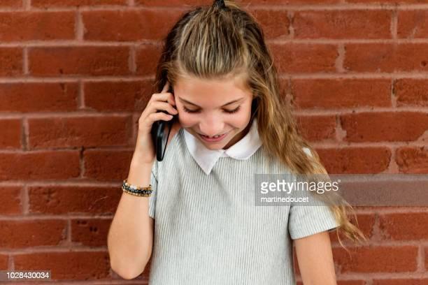 """leuk preteen meisje met mobiele telefoon buitenshuis op een bakstenen muur. - """"martine doucet"""" or martinedoucet stockfoto's en -beelden"""