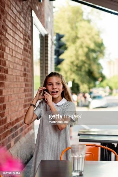 """leuk preteen meisje met mobiele telefoon buiten op de stoep van de stad. - """"martine doucet"""" or martinedoucet stockfoto's en -beelden"""