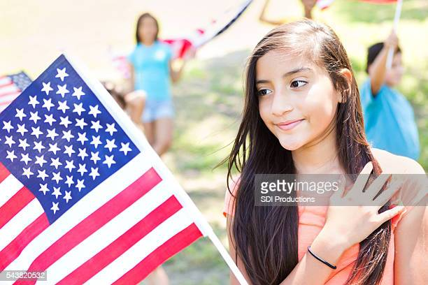 Cute preteen Hispanic girl with American flag at parade