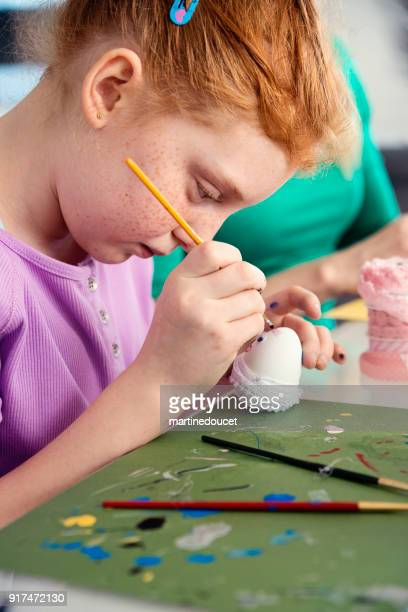 Cute preteen redhead girl crafting Easter decorations at home.