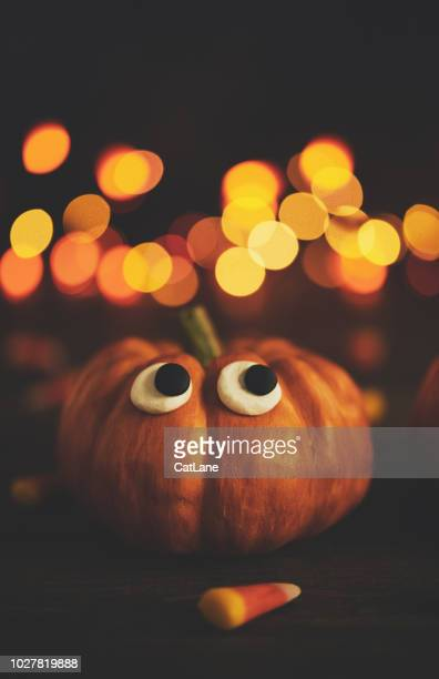 cute pumpkin character with handmade expression and holiday lights - candy corn stock photos and pictures
