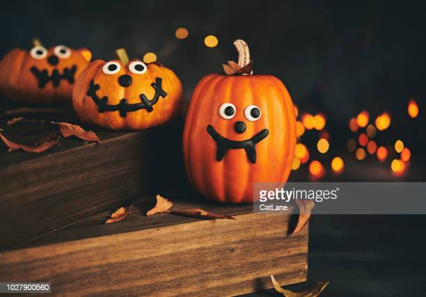 cute pumpkin characters with handmade expressions and holiday lights - jack o' lantern stock photos and pictures