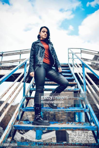 cute punk female in leather pants standing on rusted bridge steps - punk music stock pictures, royalty-free photos & images