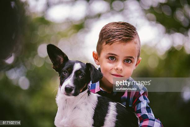 Cute puppy and mischievous boy looking at camera in nature