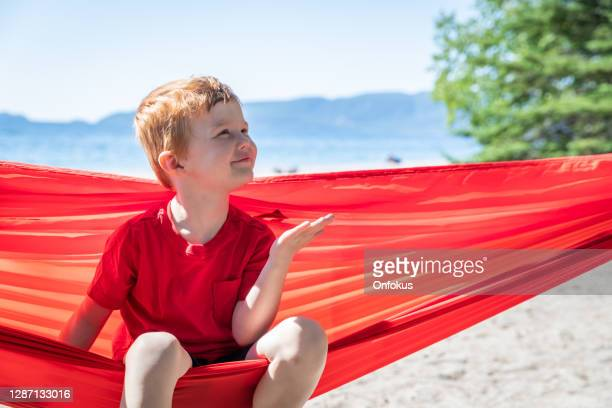 cute redhead child having fun in red hammock at campground in summer - lake superior provincial park stock pictures, royalty-free photos & images