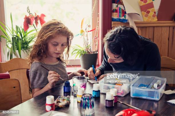 Cute redhead girl and aunt doing craft project at home.