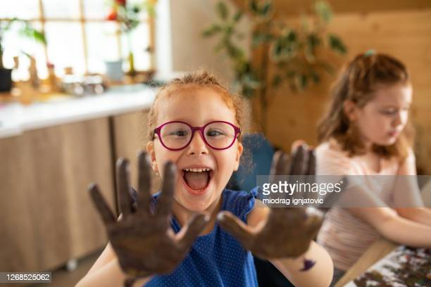 cute redhead girl showing her hands while finger painting with her friend at home - 4 girls finger painting stock pictures, royalty-free photos & images