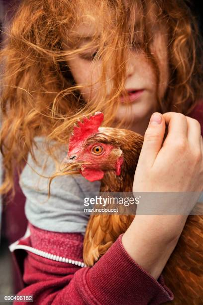 Cute redhead little girl holding a hen with wind.