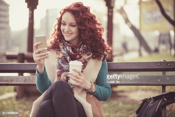 cute redhead with smart phone and coffee to go - creole ethnicity stock pictures, royalty-free photos & images