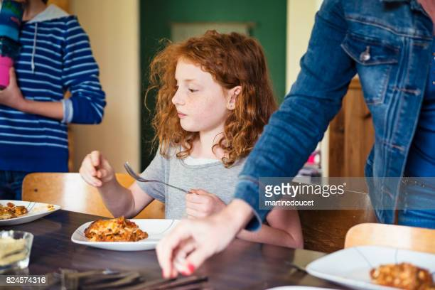 Cute redhead young girl about to eat lasagna at home.