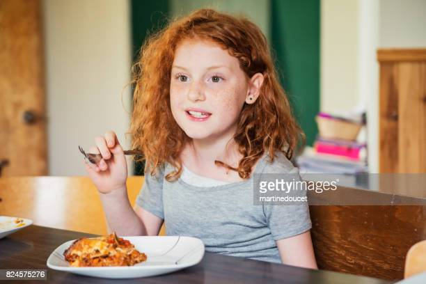 cute redhead young girl about to eat lasagna at home. - lasagna stock pictures, royalty-free photos & images