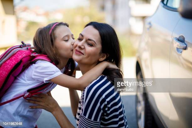 cute school girl kissing mother - first day of school stock pictures, royalty-free photos & images