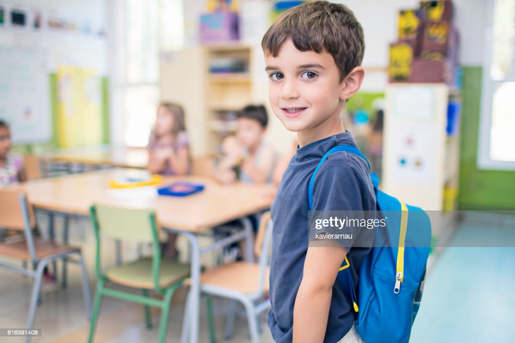 Cute schoolboy carrying backpack in classroom : Stock Photo