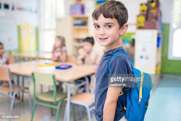Cute schoolboy carrying backpack in classroom