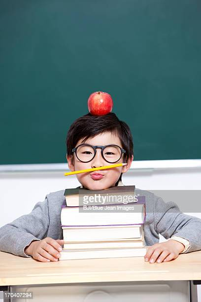 Cute schoolboy in classroom with an apple on head