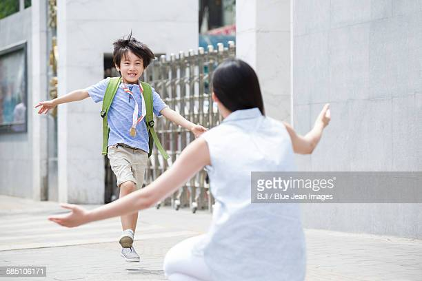 Cute schoolboy running to his mother