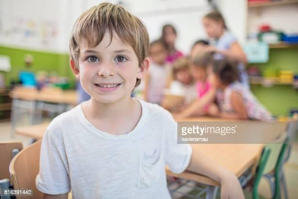 Cute schoolboy sitting at desk in classroom