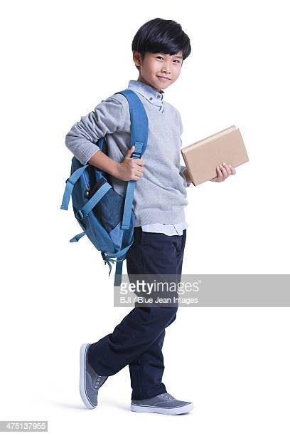 Cute schoolboy with book in hand