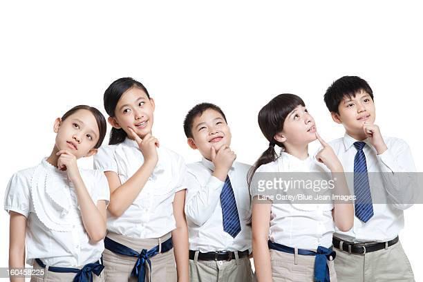 Cute schoolchildren thinking with hand on chin
