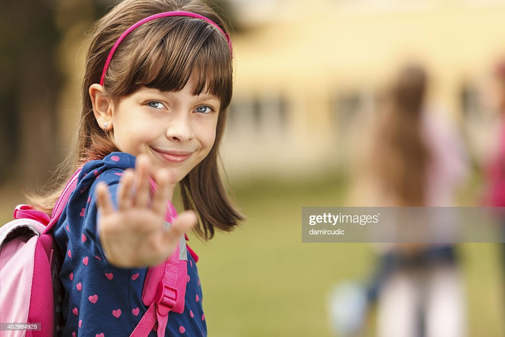 Cute schoolgirl in front of the school : Stock Photo