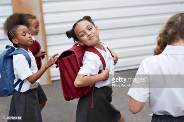 cute schoolgirl looking to camera while walking from school with friends - schuluniform stock-fotos und bilder