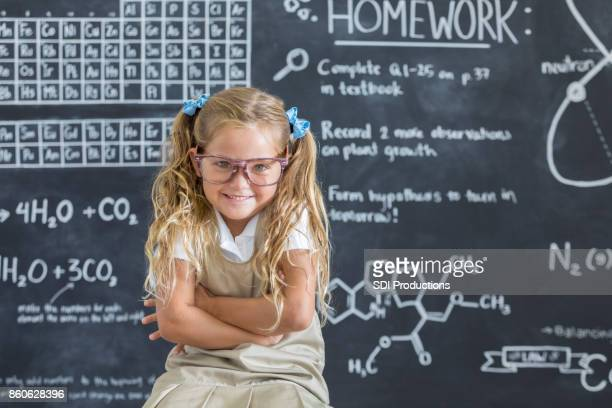 cute schoolgirl sits in front of a chalkboard in a classroom - child prodigy stock pictures, royalty-free photos & images