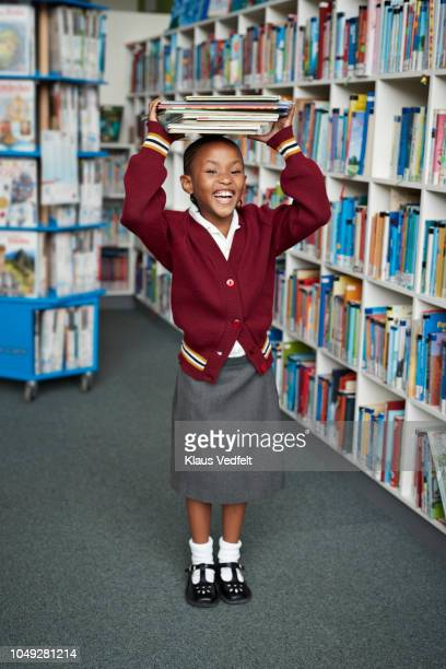 cute schoolgirl smiling & balancing stack of books on the head at library - schoolgirl stock pictures, royalty-free photos & images