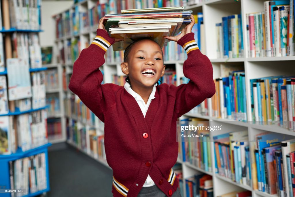 Cute schoolgirl smiling & balancing stack of books on the head at library : Stock-Foto