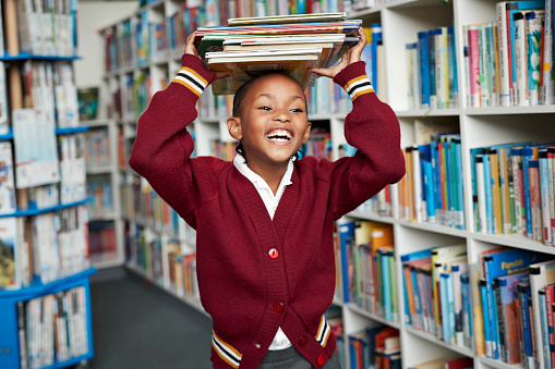 Cute schoolgirl smiling & balancing stack of books on the head at library - gettyimageskorea