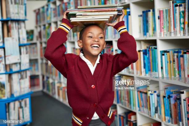 cute schoolgirl smiling & balancing stack of books on the head at library - schoolkinderen stockfoto's en -beelden
