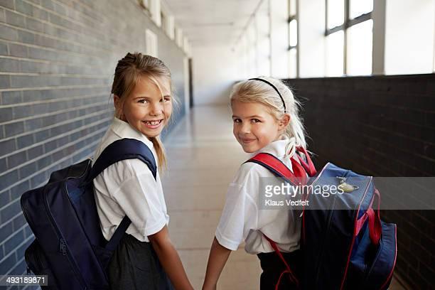 Cute schoolgirls holding hands in corridor