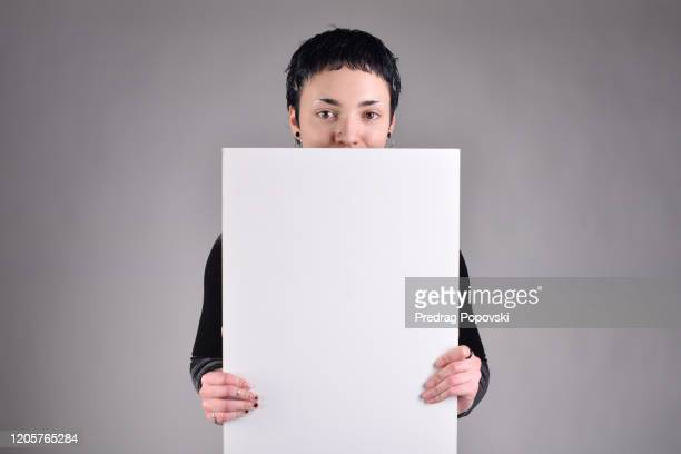 cute short haired young beautiful woman with short hair holding blank white sign on studio background - person holding blank sign stock pictures, royalty-free photos & images
