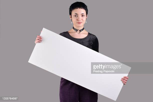 cute short haired young modern woman with short hair in fashionable clothes holding blank white sign on studio background - person holding blank sign stock pictures, royalty-free photos & images