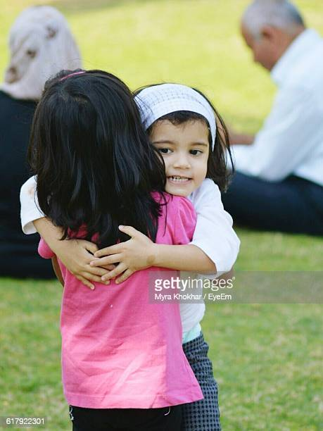 cute sibling hugging on field - only girls stock pictures, royalty-free photos & images