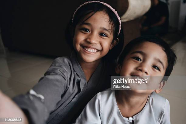 cute sibling smiling while taking selfie - eid ul fitr photos stock pictures, royalty-free photos & images