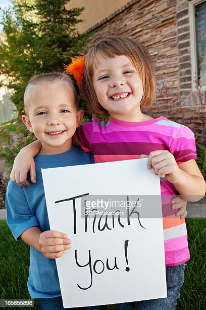 cute siblings holding a thank you sign - thank you phrase stock pictures, royalty-free photos & images