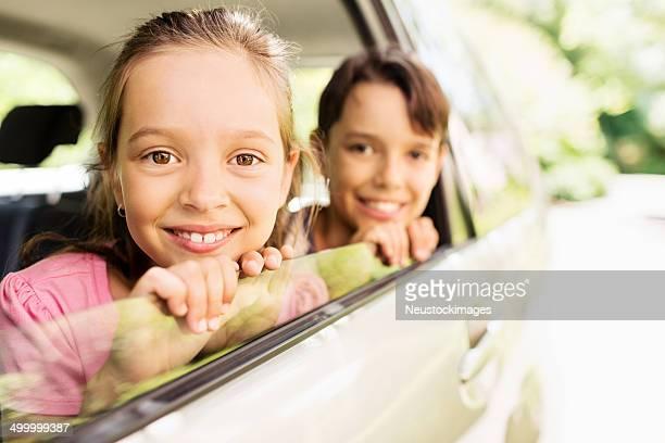 Cute Siblings Looking Through Car Window