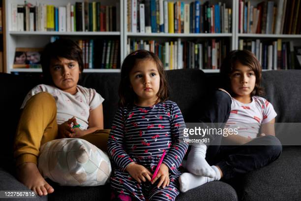cute siblings watching tv while sitting on sofa against bookshelf in living room at home - sister stock pictures, royalty-free photos & images