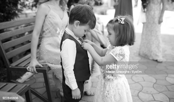 Cute Sister Adjusting Brother Tie With People In Background During Wedding