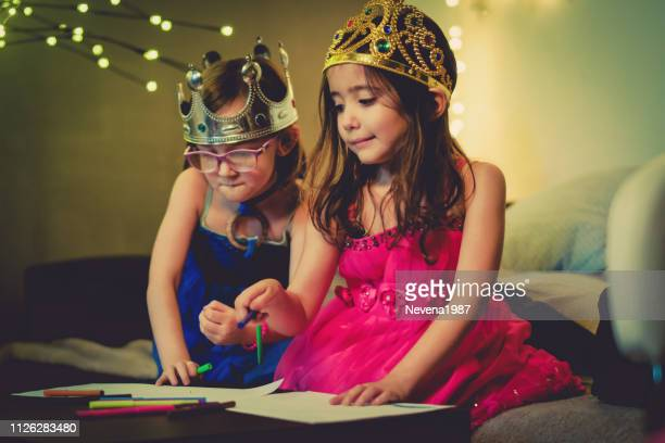 cute sisters creating pictures at home - princess stock pictures, royalty-free photos & images