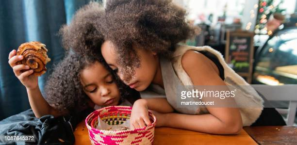 cute sisters eating cinnamon bun in restaurant in winter. - sweet bun stock pictures, royalty-free photos & images