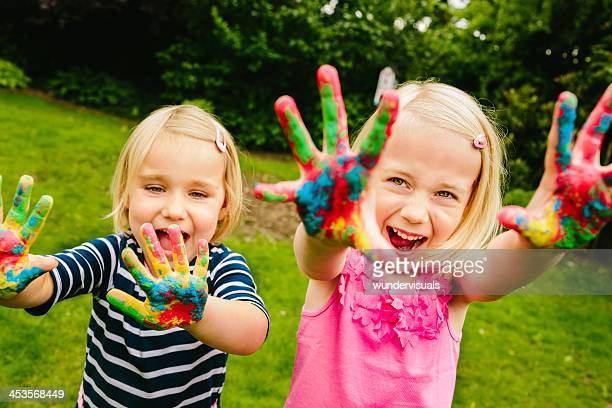cute sisters having fun with finger paint - art stock pictures, royalty-free photos & images