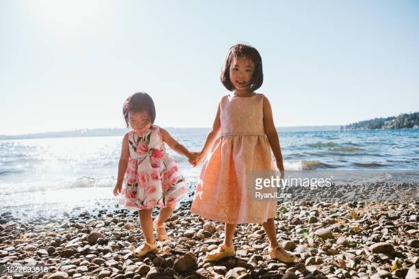 cute sisters hold hands on rocky beach - dress stock pictures, royalty-free photos & images